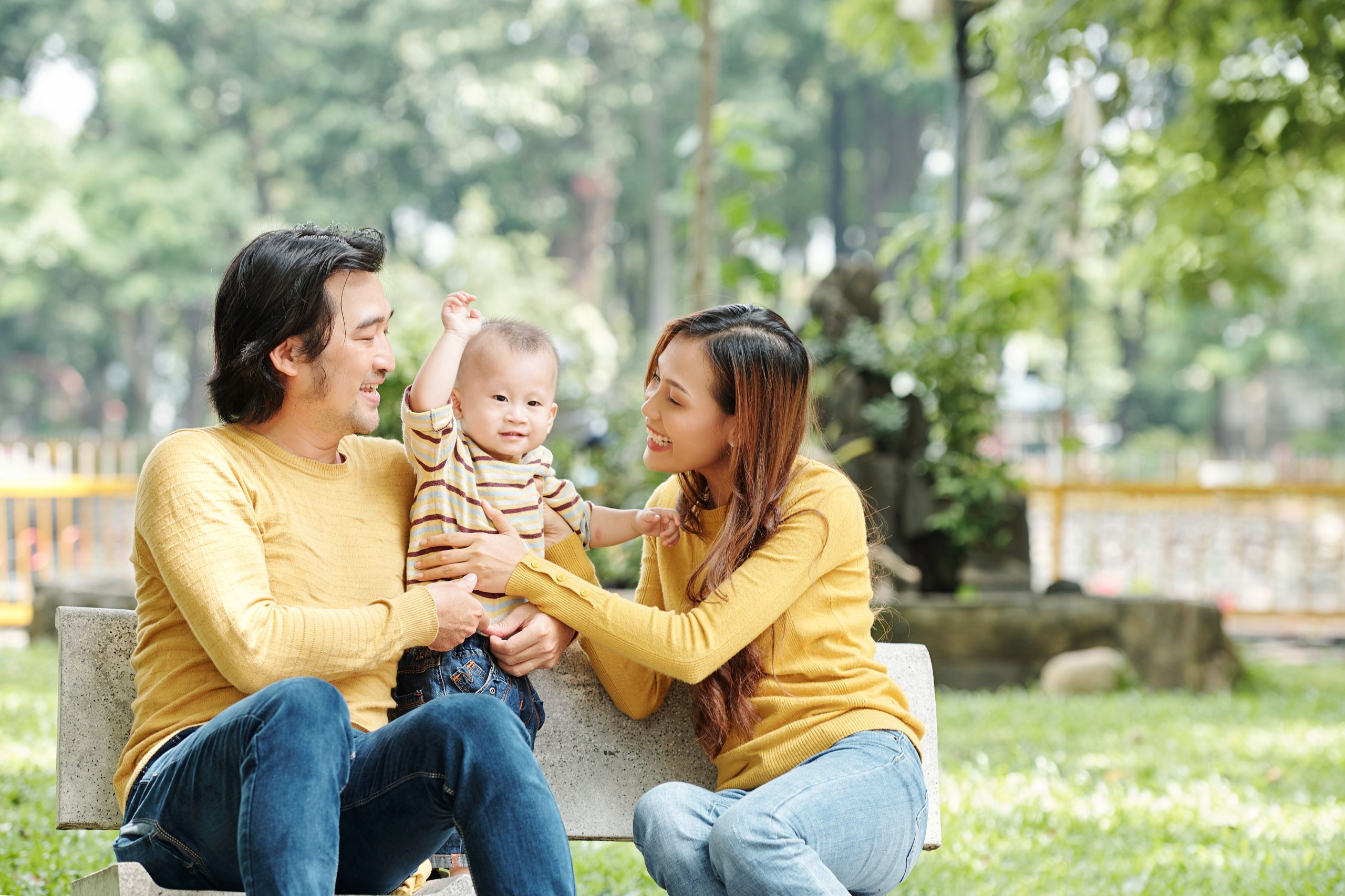 Happy young Vietnamese man and woman sitting on bench in park and adjusting sweater of thier little son